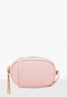 pink quilted cross body bag with tassel trim