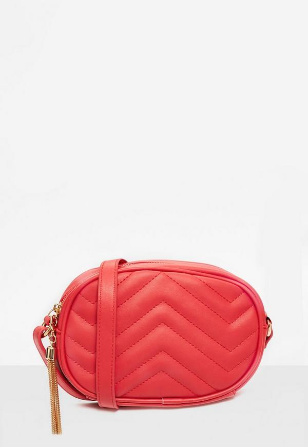 red quilted cross body bag with tassel trim