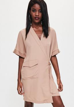Beżowa kopertowa sukienka z wiązaniem po boku i ozdobną kieszonką