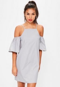 Niebieska sukienka z wyciętymi ramionami i falbankami na rękawach