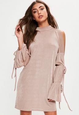 Beżowa owersajzowa sukienka z wyciętymi ramionami i ozdobnym wiązaniem na rękawach