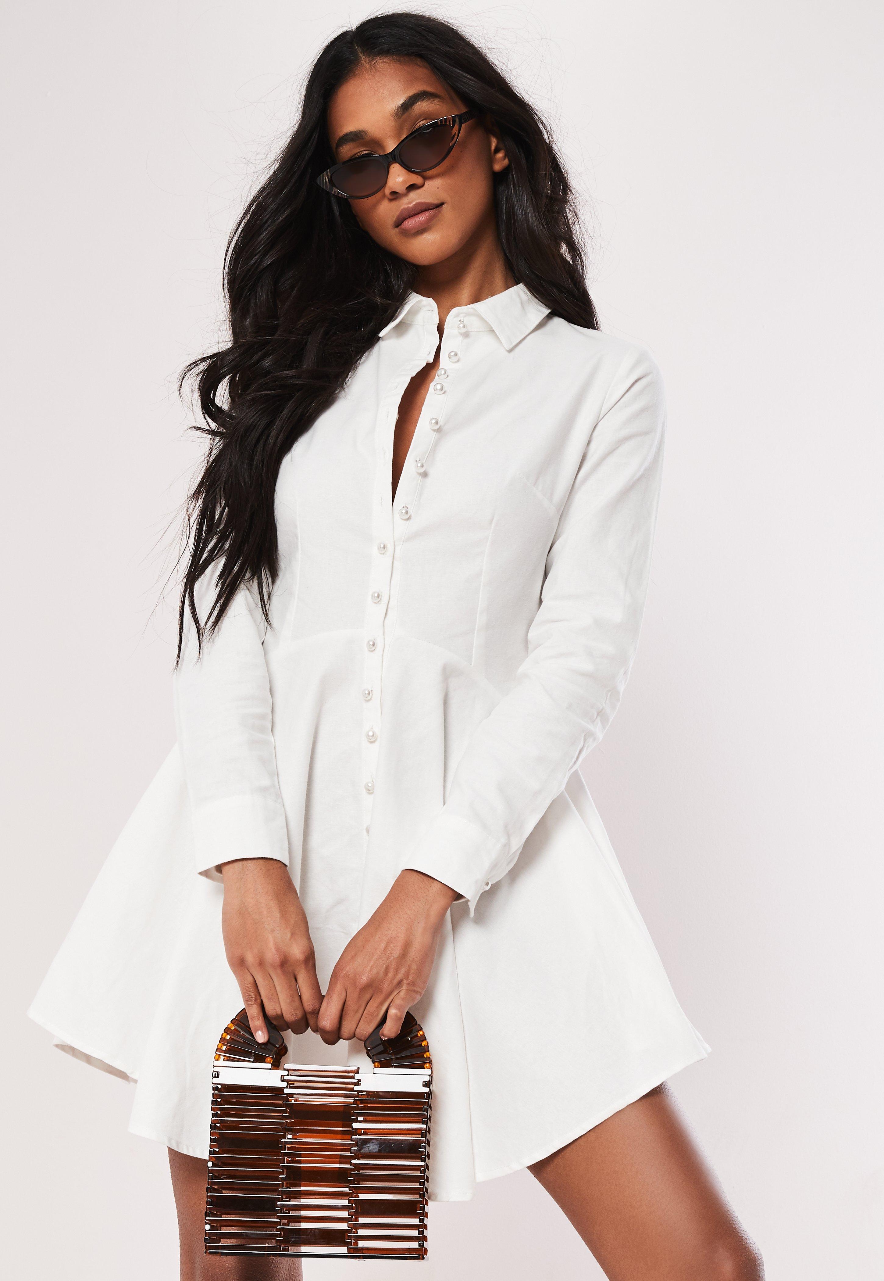 Biała rozkloszowana sukienka zapinana na guziki perełki