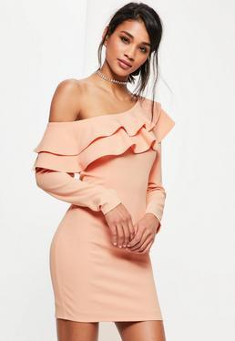 Różowa dopasowana sukienka opadająca na jedno ramię z ozdobnymi falbanami