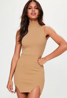 Beżowa dopasowana sukienka z ozdobnymi rozporkami i golfem