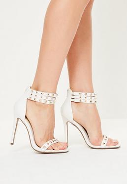 Białe sandałki na szpilce z ozdobnymi paskami i ćwiekami