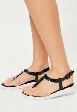 Sandalias planas con tiras en t con tachuelas en negro
