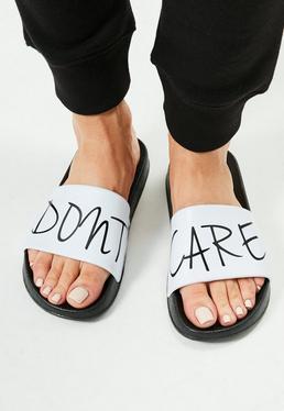 Białe wsuwane klapki z napisem Don't Care