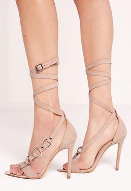 Sandalen mit Metallakzenten und Wickelbändern in Nude