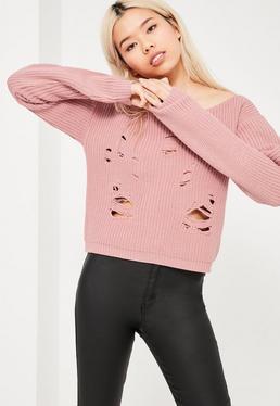 Różowy poszarpany sweterek z dzianiny opadający na jedno ramię