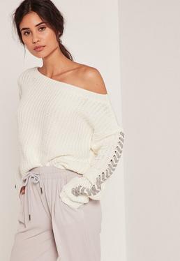 Biały sweter z odrytym ramieniem i ozdobnymi wiązaniami na rękawach