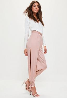 Różowe satynowe spodnie rozcięte po bokach i wiązane przy kostkach