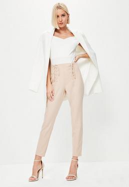 Różowe spodnie cygaretki z ozdobnymi gorsetowymi wiązaniami po bokach