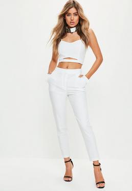 Białe spodnie cygaretki z falbankami na kieszonkach