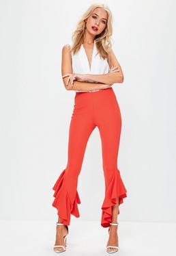 Pomarańczowe spodnie cygaretki z asymetrycznymi falbankami
