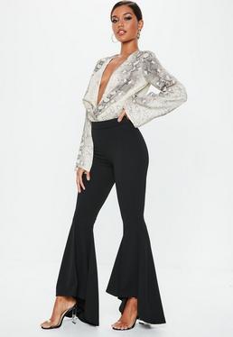 Czarne asymetryczne spodnie cygaretki zakończone szerokimi falbanami