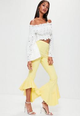 Żółte asymetryczne spodnie cygaretki z ozdobnymi falbanami