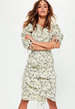 Kremowa sukienka midi w kwieciste wzory z ozdobnym pomarszczeniem po bokach