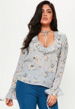Niebieska bluzka w kwieciste wzory z falbanami i wiązaniem an szyi